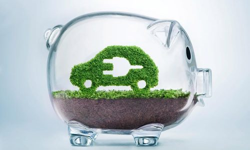 Grass growing in the shape of a car with a cut out plug, inside a transparent piggy bank, symbolising the need to invest in alternative fuel solutions.